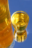 Shot and Bottle. Yellow shot and bottle on blue backdrop Royalty Free Stock Photography