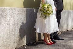 A shot of bride and groom's feet leaned against a wall on a sunny wedding day Royalty Free Stock Photos