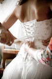 Shot of bridesmaid tying corset on bridal dress Stock Photo