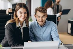Shot of business man and woman at work desk looking at camera and working with computer. Focused business team working together in royalty free stock photo