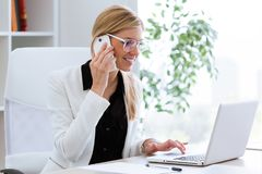 Business young woman talking on the mobile phone while using her laptop in the office. Royalty Free Stock Photos