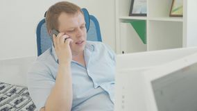 Shot of a businessman using a desktop pc while talking on mobile phone. Shot of a businessman looking to monitor of desktop pc while talking on mobile phone stock video