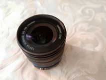 A shot of a camera lens with blue strip on a white fabric, Samsung NX series lens royalty free stock images