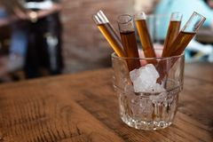 Shot of candy vodka in glass tube inside glass with ice royalty free stock photography