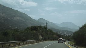Shot of car passing on the highway to the mountains. Natural travel speed stock video footage