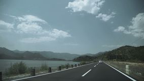 Shot of car passing on the highway to the mountains. Natural travel speed stock footage
