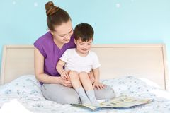 Shot of caring mother on maternity leave and small boy read fairy tale before sleep, pose at bed, view photos, enjoy domestic. Atmosphere, like reading royalty free stock photo