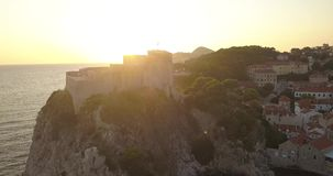 Aerial 4K - Castle on the coastline of Dubrovnik, Croatia at Sunset. A shot of the castle Loverjnac. Initially the castle blocks the sunset behind it but the stock video