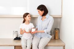 Shot of cheerful mother and daughter sit together at kitchen table, drink hot tea in morning, have pleasant friendly royalty free stock images