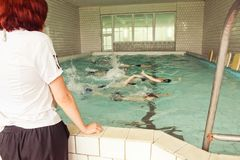 Elementary school children within swimming skills lesson. stock image