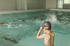 Elementary school children within swimming skills lesson. stock photo