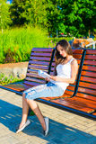 A shot of a college student reading a book. Girl sitting on a bench and reading a book in park Stock Images