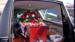 Shot of a colorful casket in a hearse or chapel before funeral or burial at cemetery. Closeup shot of a colorful casket in a hearse or chapel before funeral or stock footage