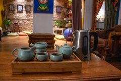 Ceramic gong fu cha tea kit for tea ceremony, placed on a tea boat with a kettle. Shot in a colorful living room environment stock image