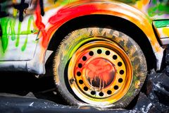 Shot of colorfully painted car tire on an old, crashed car wreck. Kids are having fun, making drawings and graffiti art, paint on wreck and tires with green royalty free stock photo