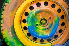 Shot of colorfully painted car tire on an old, crashed car wreck. Kids are having fun, making drawings and graffiti art, paint on wreck and tires with green stock photography