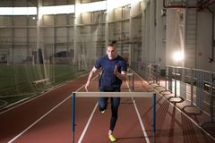 Concentrated male track and field athlete hurdling.Indoor training. The shot of concentrated male track and field athlete hurdling.Indoor training royalty free stock photography