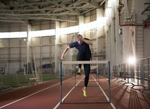 The shot of concentrated male track and field athlete jumping over the hurdle. Indoor training stock images
