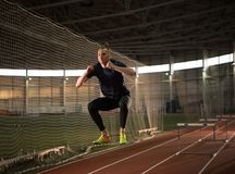 Concentrated male track and field athlete warming up before hurdling training.Indoor training. The shot of concentrated male track and field athlete warming up stock photography