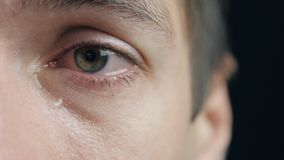 Shot of Crying man with tears in eye closeup. Crying man with tears in eye closeup stock footage