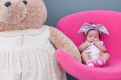 A shot of a cute baby girl with purple headband and big teddy bear while sleeping and playing on the pink chair /  Focus at infant Stock Photos