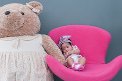 A shot of a cute baby girl with purple headband and big teddy bear while sleeping and playing on the pink chair /  Focus at infant Stock Images