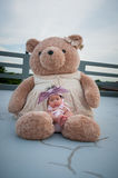 A shot of a cute baby girl with purple headband while sleeping and playing with big teddy bear on the rooftop /  Focus at infant g Royalty Free Stock Photography