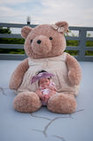 A shot of a cute baby girl with purple headband while sleeping and playing with big teddy bear on the rooftop /  Focus at infant g Royalty Free Stock Images