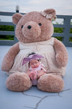 A shot of a cute baby girl with purple headband while sleeping and playing with big teddy bear on the rooftop /  Focus at infant g Stock Image