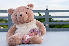 A shot of a cute baby girl with purple headband while sleeping and playing with big teddy bear on the rooftop /  Focus at infant g Stock Photos