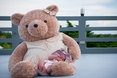 A shot of a cute baby girl with purple headband while sleeping and playing with big teddy bear on the rooftop /  Focus at infant g Royalty Free Stock Photo