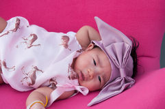 A shot of a cute baby girl with purple headband while sleeping and playing on the pink chair /  Focus at infant girl Stock Image