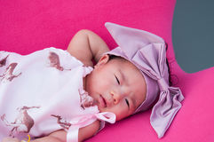 A shot of a cute baby girl with purple headband while sleeping and playing on the pink chair /  Focus at infant girl Stock Photo