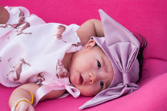 A shot of a cute baby girl with purple headband while sleeping and playing on the pink chair /  Focus at infant girl Royalty Free Stock Image