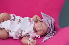 A shot of a cute baby girl with purple headband while sleeping and playing on the pink chair /  Focus at infant girl Royalty Free Stock Photography