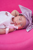A shot of a cute baby girl with purple headband while sleeping and playing on the pink chair /  Focus at infant girl Royalty Free Stock Images