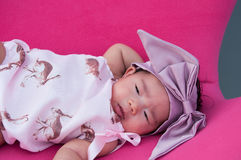 A shot of a cute baby girl with purple headband while sleeping and playing on the pink chair /  Focus at infant girl Royalty Free Stock Photos