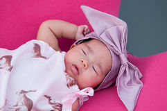 A shot of a cute baby girl with purple headband while sleeping and playing on the pink chair /  Focus at infant girl Stock Photos
