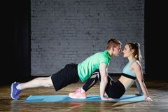 Shot of a cute couple kissing each other while doing exercise in gym royalty free stock photo