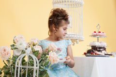 Shot of cute little lady drinking tea in studio Royalty Free Stock Photo