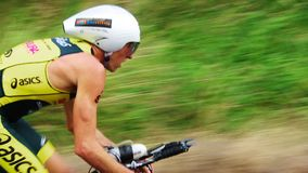 A cyclist in a fast paced mode. A shot of a cyclist triathlete peddling hard uphill and looking back at his competitors stock footage