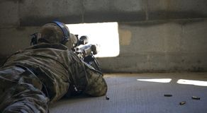 Shot from the Dark. Sniper using a small window to secretly take a long shot Stock Photography