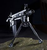 Shot in the dark. Modern assault rifle with a bipod that is set up in the dark Stock Image