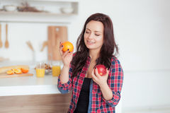 Shot of a dark haired caucasian woman comparing apples to oranges royalty free stock photography
