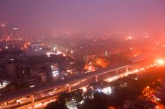 Delhi Noida Gurgaon with heavy pollution smog at dusk. Shot of Delhi Noida Gurgaon with heavy toxic smog and fog covering it. A metro station with tracks, homes stock image