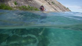 A diver standing on sea rocks. A shot of a diver wearing a snorkeling mask, a white diving garment and a blue shorts walking on sea rocks stock video footage
