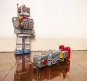 Shot down robots. Shot down concept with retro tobot toys on a wooden floor with reflection Stock Photo