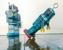 Shot down robots. Shot down concept with retro tobot toys on a wooden floor with reflection Royalty Free Stock Images