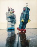 Shot down robots. Shot down concept with retro tobot toys on a wooden floor with reflection Stock Image