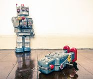 Shot down robots. Shot down concept with retro tobot toys on a wooden floor with reflection Royalty Free Stock Image